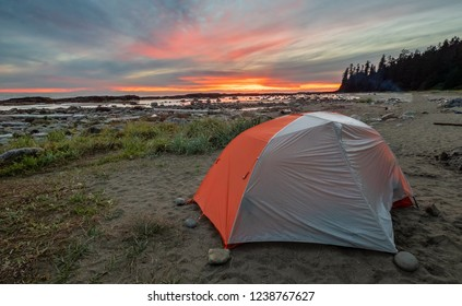 Backpacking tent on a beach with amazing dramatic sunrise in the distance.
