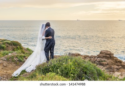 backs of bride and groom against landscape at dawn in italy