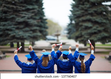 Backs of ecstatic students in graduation gowns holding diplomas