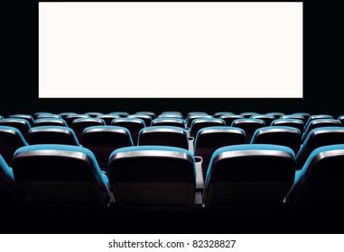 Backs of empty blue seats in a movie theater with a white screen
