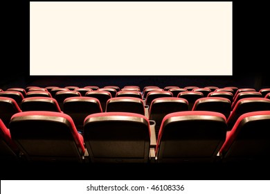 Backs of empty red seats in a movie theater with a white screen