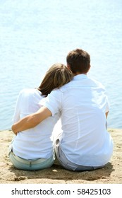 Backs of serene couple sitting on sandy shore in front of blue water