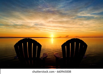 The backs of two adirondack chairs waiting at the end of a dock to enjoy the early morning summer sunrise