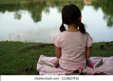 backside Asian child cute little girl Sitting  In the park