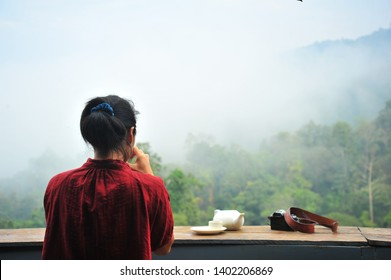 Backside of Asian Woman Wear Red Shirt Sit and Drinking Hot Tea at The Wooden Deck Outside Cafe with Beautiful View of Mountain and Mist
