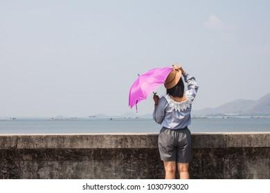 backside asian women wear umbrella with sunlight rays