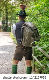 backside of bavarian man with backpack walking on path