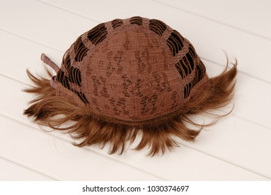 backside of brown wig, inside, the internal side of wig, curly hair is on white table