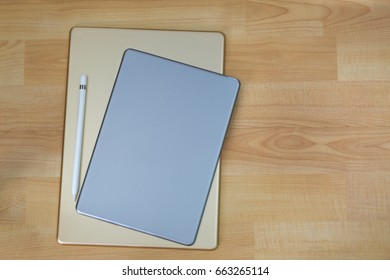 Backside of gold silver ipad pro tablet computer next to white pencil pen on wooden background with copyspace