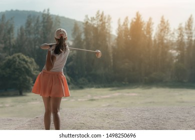 Backside of Golfers hit sweeping and keep golf course in the summer, she does exercise for relax time