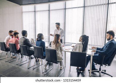 Backside of group of diverse multiracial applicants for a vacant post or corporate job sitting in a long line before HR specialist explaining test task over panoramic windows background.
