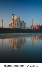Backside of the majestic Taj Mahal and smaller red mosque glowing with reflected morning sunrise light in the calm rear Jamuna river on a clear blue sky day in Agra, India. Vertical copy space