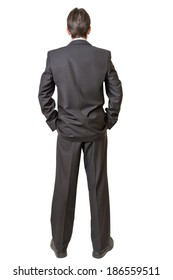 Backside of man in black suit keeping hands in pockets isolated on white background