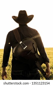 the backside of a modern cowboy with is guitar at the countryside of America on a sunset evening with lots of sun beams
