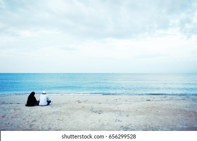 Backside of Muslim man and woman sitting together on the beach, looking forward to the blue sea. Halal tourism of Muslim couple with seascape background in summer on Ramadan period. Copy space.