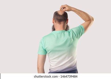 Backside portrait of middle aged bald man with beard in light green t-shirt standing, scratching his head or thinking about something. indoor studio shot, isolated on grey background.