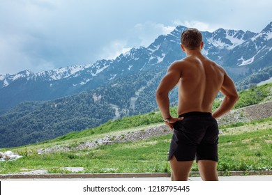 Backside of tall muscular caucasian bodybuilder with naked torso standing in over mountain and sky background. Handsome strong man showing his muscles promoting active sport healthy lifestyle