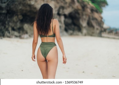Backside view of beautiful girl with sexy ass walking at the ocean beach. Model in green swimsuit at vacation