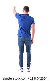 Backside view of casual adult man showing way or pushing interactive touch screen button with left hand. Full body isolated on white background.