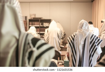 Backside view of congregants in a Jewish synagogue wrapped in prayer shawls during prayer