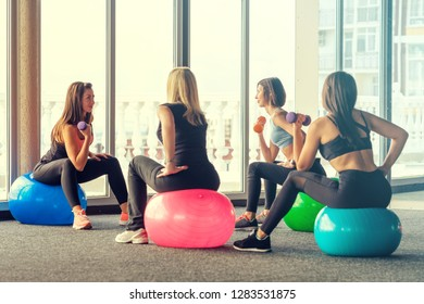 Backside view cute young women in sport wear do exercise with dumbbells in their hands sitting on fitball and listen to fitness instructor in gym against panoramic windows with bright sunlight
