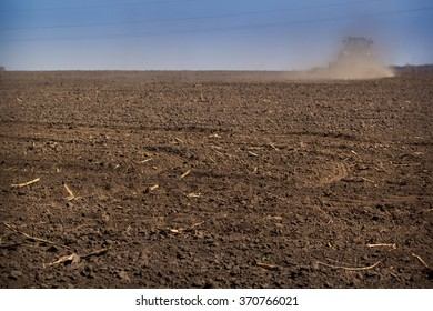 backside view distant tractor cultivator on big wheels raises great dust on ploughed ground on skyline