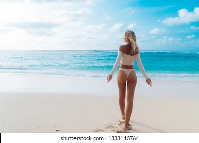 Backside view of girl with sexy booty in beige colour bikini resting on deserted beach. Beautiful model in swimwear walks along white sand on tropical island