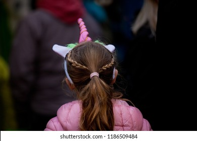 backside view of a little girl in pink jacket with dark blonde hair and plait, she wears a pink unicorn head dress