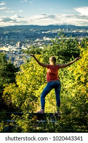 Backside view on young woman standing in city park of Oslo and enjoying beautiful panorama of the city on sunny day, Norway.
