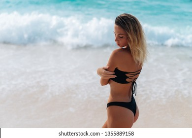 Backside view of tanned girl with sexy ass in black bikini walking on beach. Young woman traveler with perfect body on vacation. Concept swimwear
