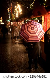 backside view of a woman at a christmas market at night with horizontally striped umbrella while it is raining