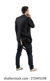Backside view of young artist looking at blank white wall.  Full body length portrait isolated over white background.