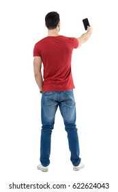 Backside view of young casual man taking photo with mobile phone. Full body length portrait isolated over white studio background.