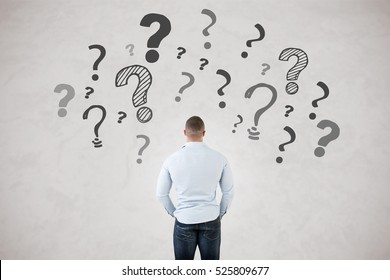 Backside of a young fit man with question marks around him, isolated in grey