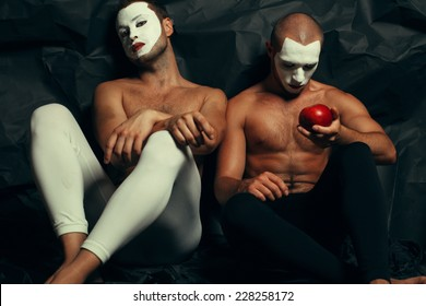 Backstage concept. Arty portrait of two circus performers in tights holding red apple, posing over black cloth. White masks on faces. Muscular bodies and perfect tan. Halloween party