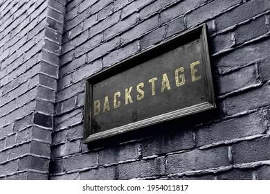 Backstage hanging signage wooden board. Business owner puts a golden black backstage sign.