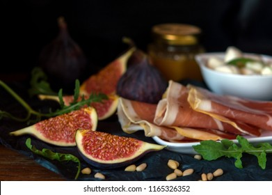 Backstage, ingredients for antipasto, salad or snacks from Parma ham, figs, mozzarella, arugula, pine nuts and balsamic with honey