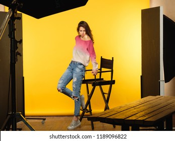 backstage photography. model posing during photoshoot. art and hobby concept. casual young beautiful brown haired girl in ripped jeans on yellow background.