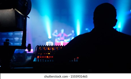 Backstage: Rear view of man manipulating audio console and lights from a stage where he performs a live performance