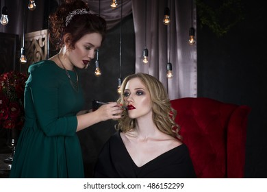 Backstage scene: makeup artist applies lipstick before the photoshoot, beautiful woman face, perfect make-up, luxurious interior