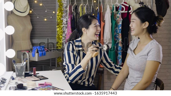 Backstage scene real moment concept. Professional female make up artist doing make up for young beautiful woman tv host preparing for show in dressing room. celebrity and beautician chatting laughing