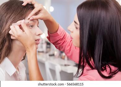 Backstage scene: visagiste at work doing glamour model makeup.
