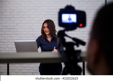 Backstage from video studio. Photografer works with camera. Woman is sitting and typing