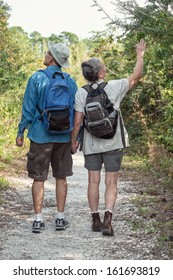 Back-view of attractive mature or senior couple holding hands while hiking on a nature trail wearing backpacks.