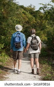 Back-view of cute mature couple hiking on nature trail while holding hands.