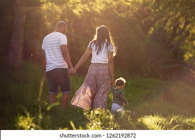 backview of family walking together in a park with young child, closeness happy together