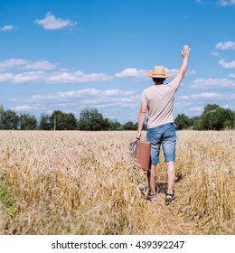 Backview of male carrying old valise over blue sky outdoors background. Man wearing hat with suitcase walking away through wheat field.