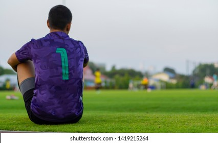 backview of male goalkeeper siting beside the green football field , boring wait for chance of substitution