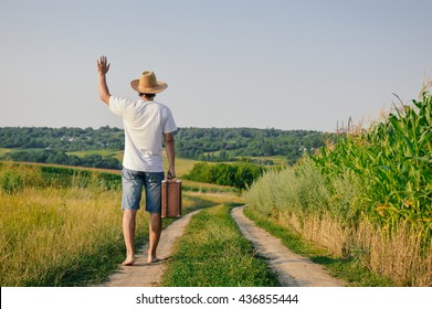 Backview of male holding old valise over blue sky outdoors background. Man wearing hat with suitcase walking away through wheat field.