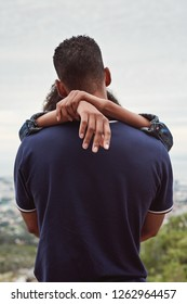 Backview of man with girlfriend's arms around his neck, couple in love hugging having a close intimate moment